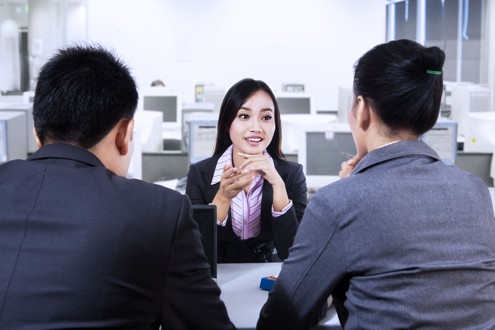 two business people having job interview with young woman